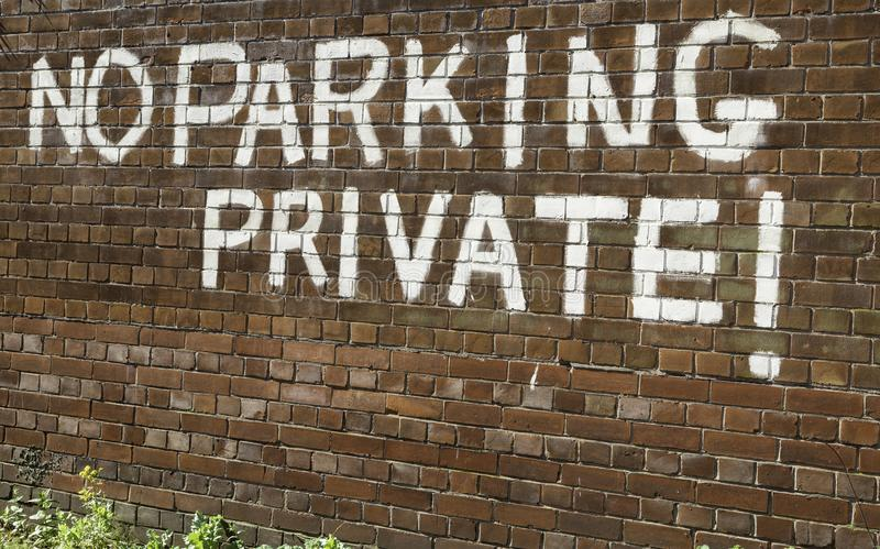 No parking private painted in large white capital letters in a b. Rick wall in Warrington Cheshire May 2018 royalty free stock photos