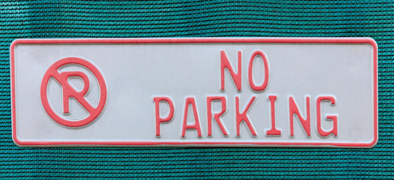 No parking sign on blue woven fabric. White and red no parking sign. Blue woven fabric background royalty free stock photo