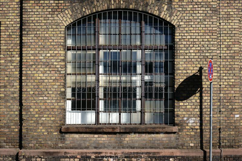 Disused factory with brick walls. A no-parking sign casts a shadow on the brick wall on the disused industrial site of an old factory with a barred window stock image