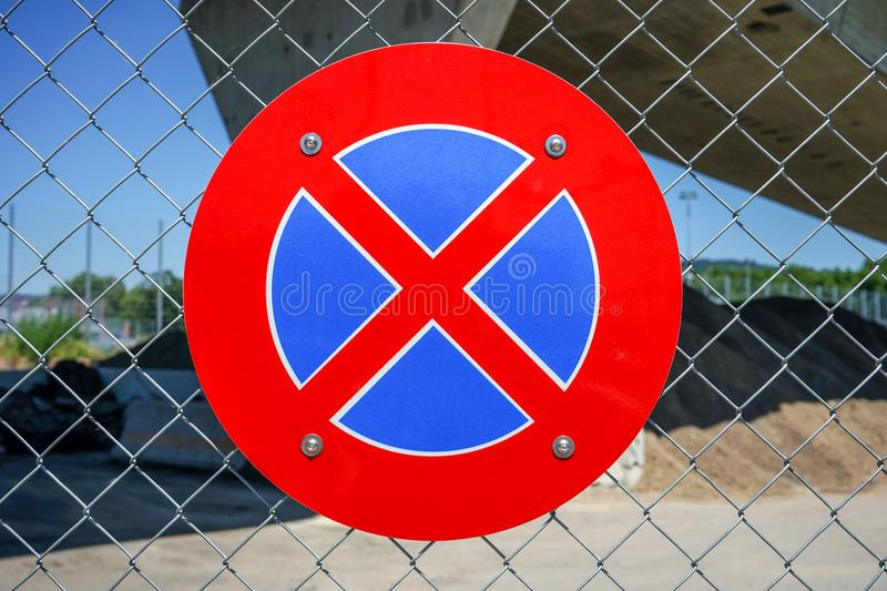 No parking sign in red and blue on metal fence. European no parking symbol on iron gate stock photo
