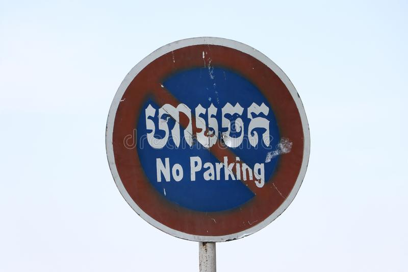 No Parking sign on sky background in Cambodian language and English royalty free stock images