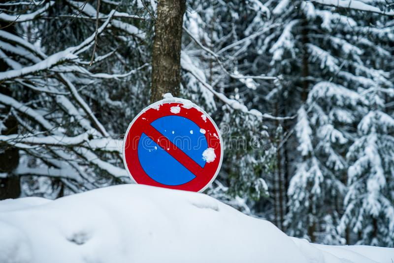 A no-parking sign in a snow pile. In winter time with a forest in the background stock photos