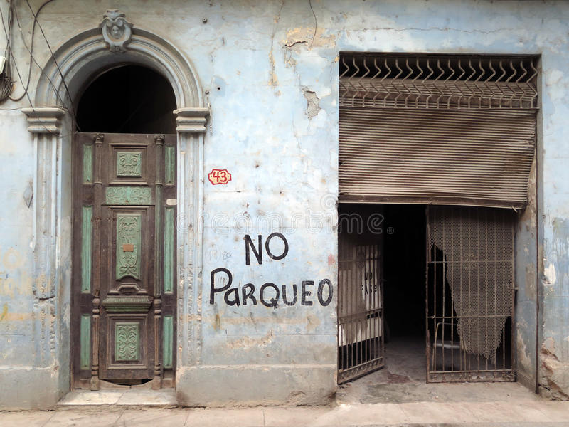No Parqueo Havana. Detail of an abandoned house in the center of Havana, Cuba: Garage entrance broken, nice wooden colonial style door. Beautiful patina. Natural royalty free stock photos