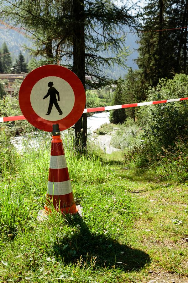 No passage sign in forest. No passage sign on traffic cone, hiking trail blocked by red and white striped band in a forest stock images