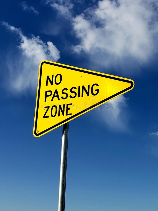 Cauction sign No passing zone sign with a blue sky background. No passing zone sign with a blue sky. Caution, dontpass, staythepath, direction, directions, drive royalty free stock image