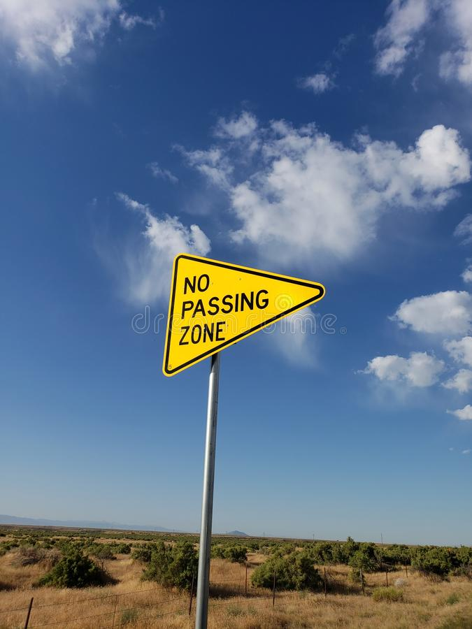 No passing zone sign standing on roadside in a rural area. Caution, dontpass, staythepath, direction, directions, drive, travelers, traveling, yellow, sky royalty free stock photo