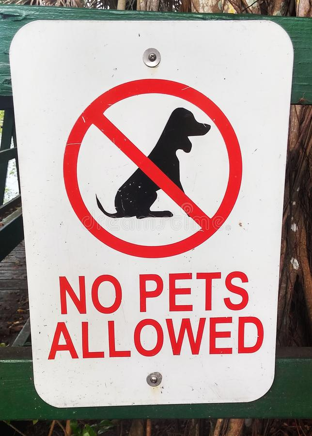 No Pets Allowed Sign. No Pets allowed metal sign at a public park attached to wooden fence stock photos