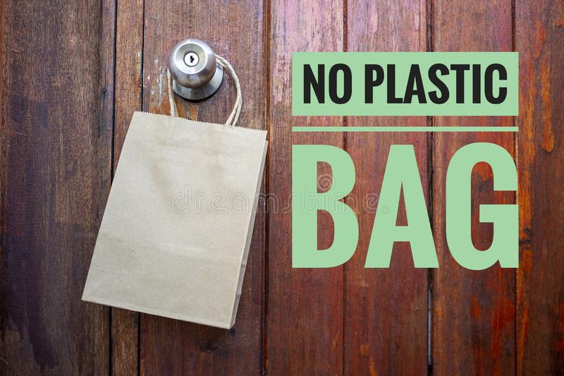 No plastic bag campaign with Empty brown paper shopping bag hanging on old wooden door stock image