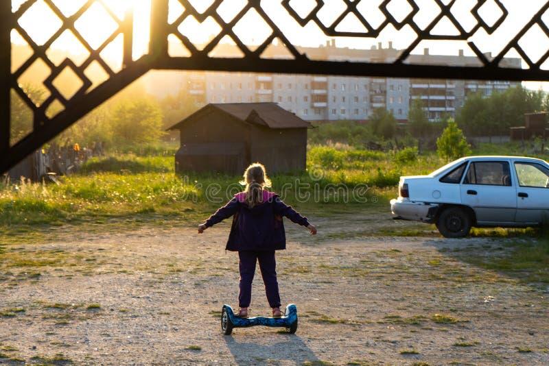No por do sol, uma menina adolescente monta um hoverboard fotos de stock royalty free