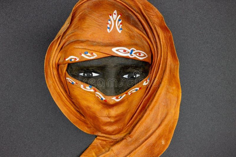 No primeiro plano uma máscara que descreve uma cara típica de uma mulher com características africanas e com burqa fotografia de stock royalty free