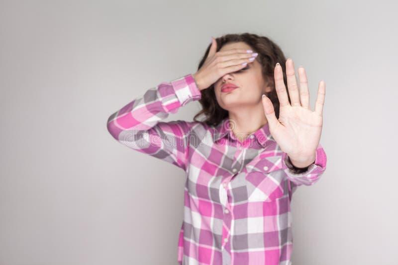 No quiero verlo muchacha confusa con la camisa a cuadros rosada s fotografía de archivo libre de regalías