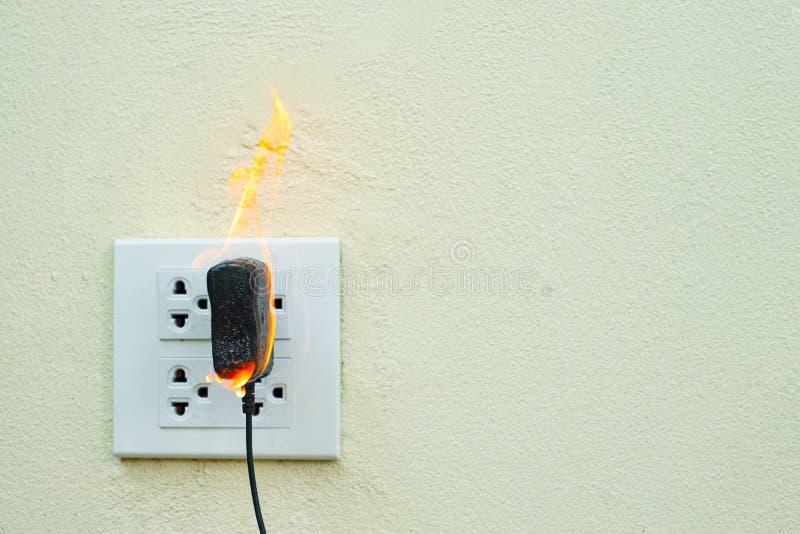 No receptáculo e no adaptador elétricos da tomada do fio do fogo no fundo branco fotografia de stock