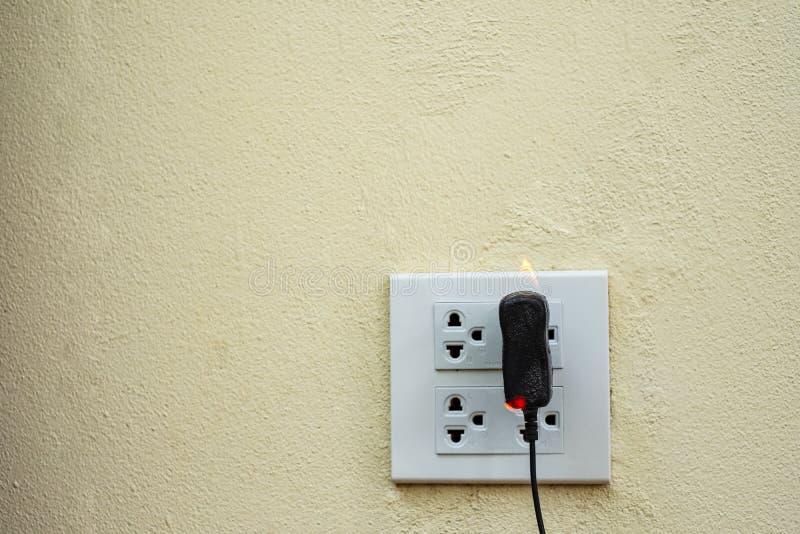 No receptáculo e no adaptador elétricos da tomada do fio do fogo no fundo branco imagem de stock