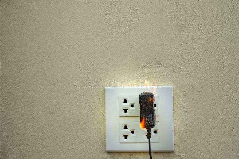 No receptáculo e no adaptador elétricos da tomada do fio do fogo no fundo branco imagens de stock