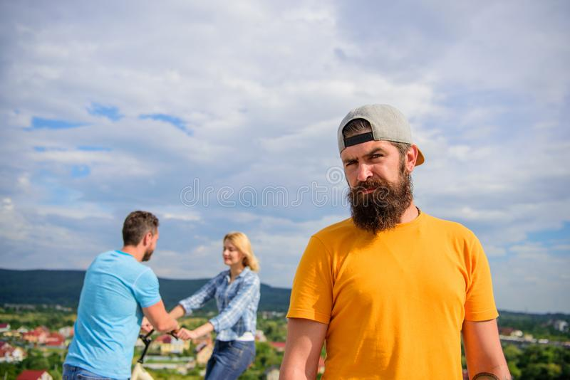 No romantic in his life. Guy adult still lonely while friends happy family life. Hipster sad face in front of couple in stock photography