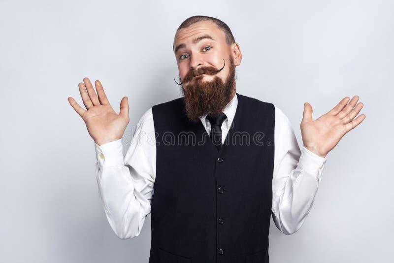 No sé Hombre de negocios hermoso con el bigote de la barba y del manillar que mira la cámara y confundido foto de archivo libre de regalías