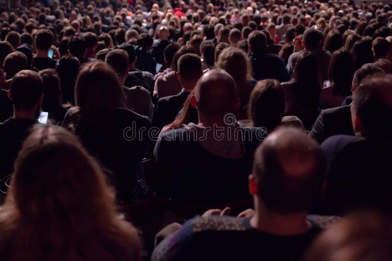 No salão escuro há uma vista da parte de trás de uma multidão de centenas de povos que sentam e que olham a tela em um cinema foto de stock