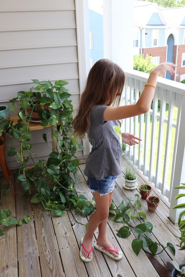 Young Girl Dreamily Spends Time on Balcony With Plants During Summer Vacation royalty free stock photo