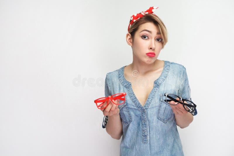 No sepa Retrato de la mujer joven de la tristeza en camisa azul casual del dril de algodón con el maquillaje, situación roja de l fotografía de archivo