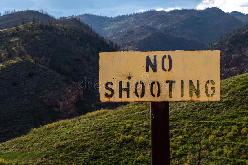 No shooting sign for guns firearms. No shooting sign banning the use of guns and firearms with an outdoor nature background in the mountains. - gun ban stock photo