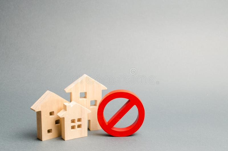 No Sign and the wooden house on an gray background. Unavailability of housing, busy or low supply. Inaccessible and expensive. Housing. Seizure and freezing of royalty free stock photos