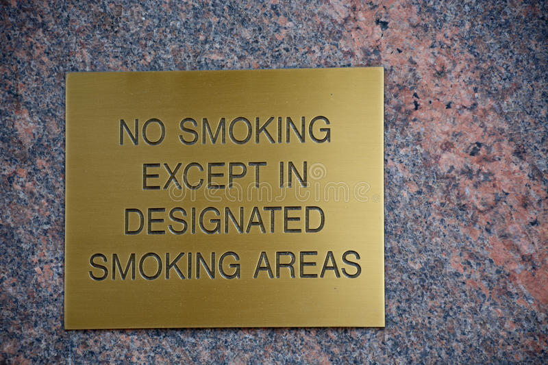 No smoking. Brass plate engraved with a no smoking warning stock photo
