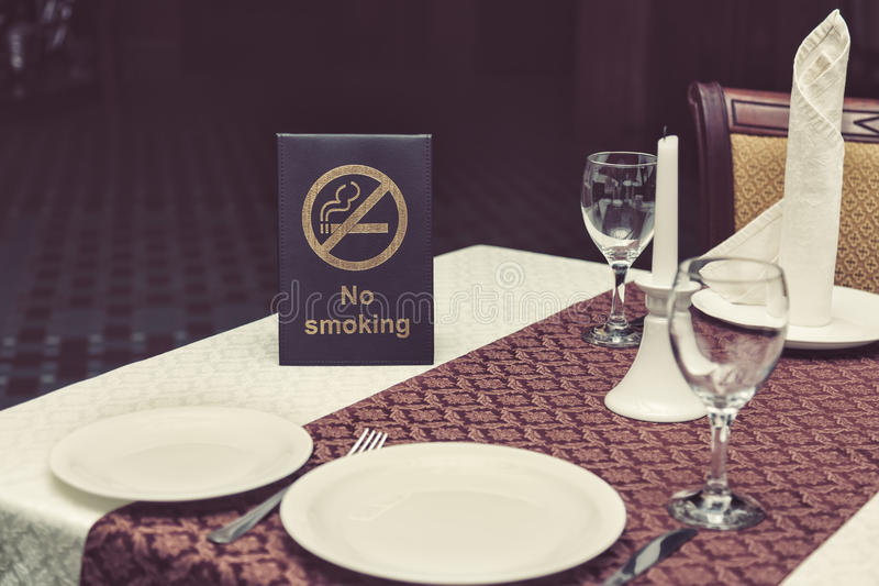 No smoking sigh on table with glasses, napkin and plates in restaurant royalty free stock images