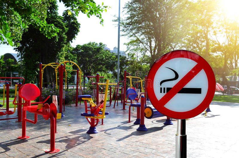 No smoking sign with colorful exercise equipment in public park stock images