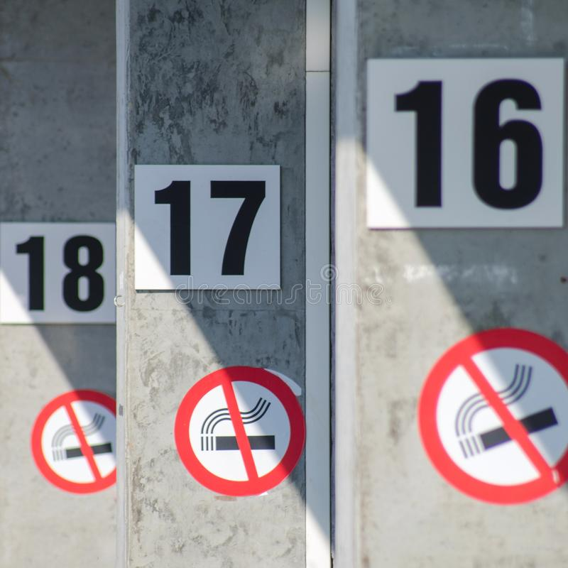 No Smoking Sign resolution in 2017. Number 16, 17, 18 on wall with sign no smoking. New Year`s resolutions concept. royalty free stock image
