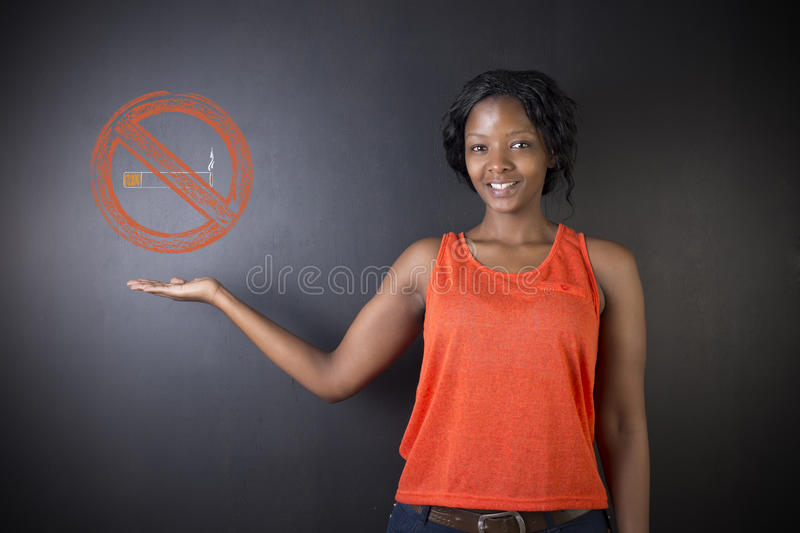 No smoking South African or African American woman. No smoking tobacco addict South African or African American woman teacher or student on blackboard background stock photo