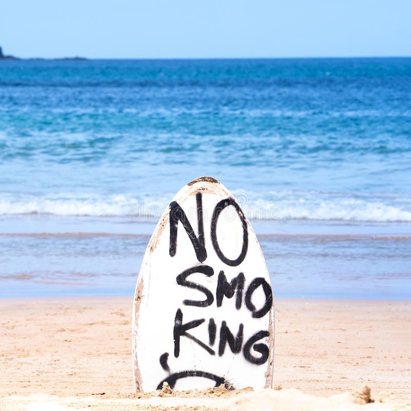 No Smoking warning sign on white surfboard at the beach in summer, concept of sea environmantal protection design, copy space,. Lifestyle royalty free stock photography