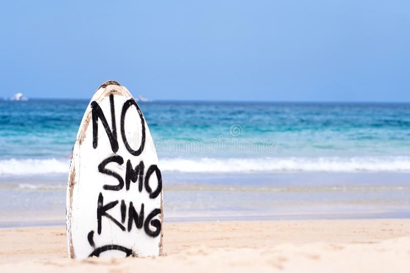 No Smoking warning sign on white surfboard at the beach in summer, concept of sea environmantal protection design, copy space,. Lifestyle stock images