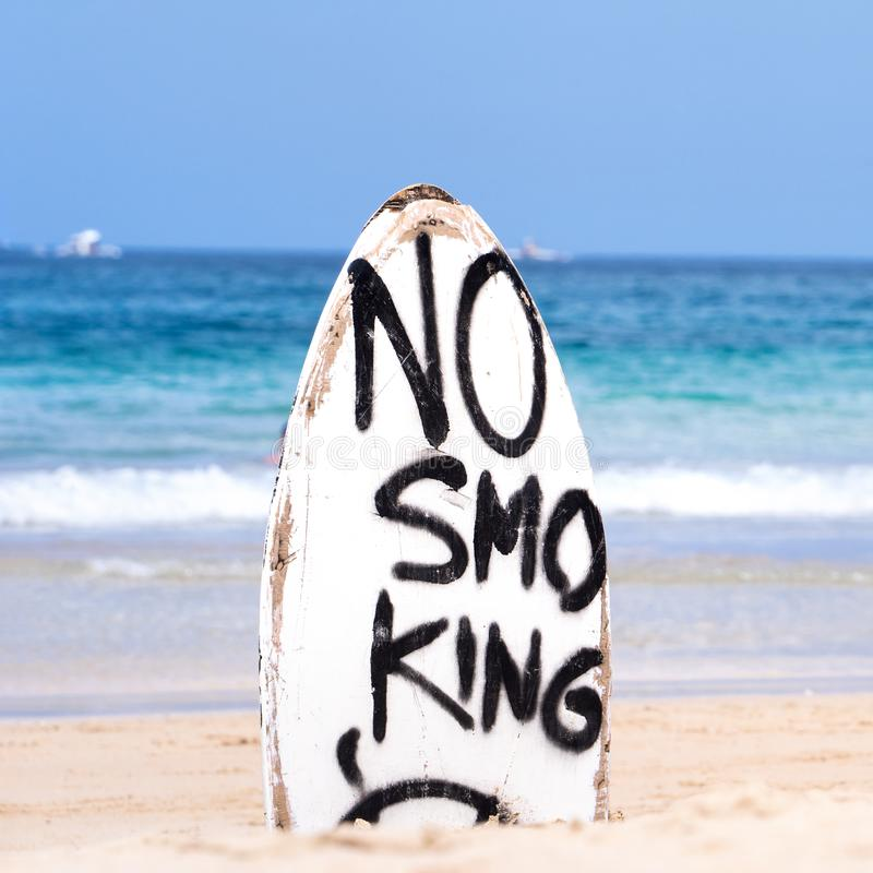 No Smoking warning sign on white surfboard at the beach in summer, concept of sea environmantal protection design, copy space,. Lifestyle royalty free stock images
