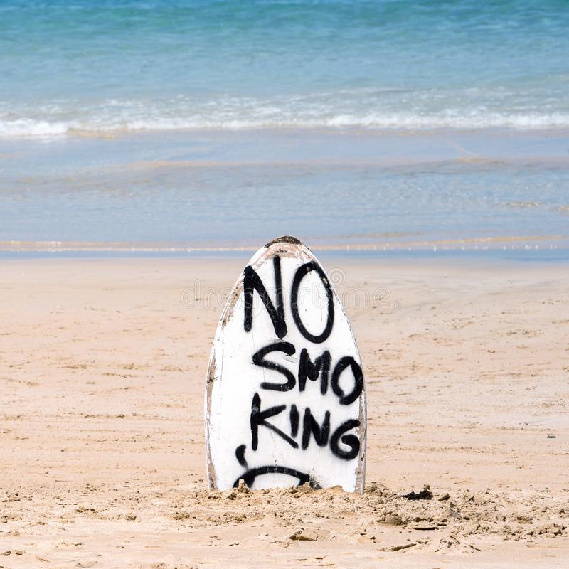 No Smoking warning sign on white surfboard at the beach in summer, concept of sea environmantal protection design, copy space,. Lifestyle royalty free stock image