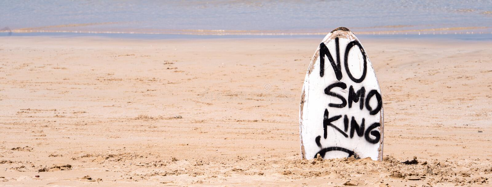 No Smoking warning sign on white surfboard at the beach in summer, concept of sea environmantal protection design, copy space,. Lifestyle stock photo