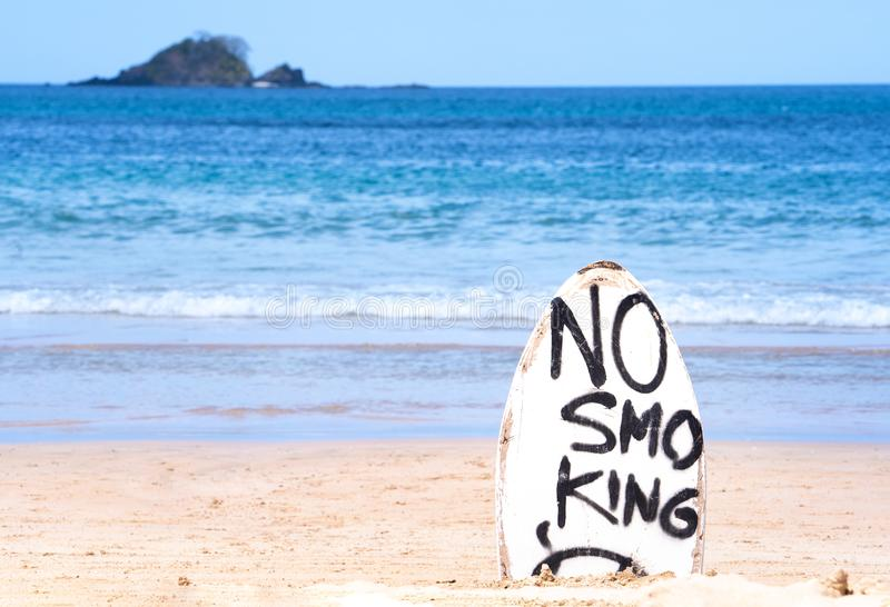 No Smoking warning sign on white surfboard at the beach in summer, concept of sea environmantal protection design, copy space,. Lifestyle royalty free stock photo