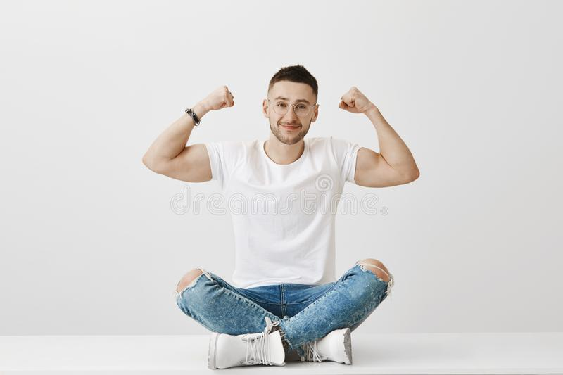 No steroids just lots of effort and power of will. Friendly-looking strong man in glasses sitting on floor while showing stock images