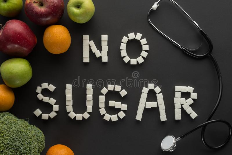 No sugar lettering made of cubes among fruits and vegetable. On black stock image