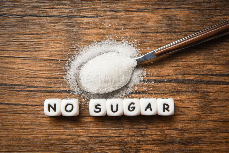 No sugar text blocks with white sugar on spoon wooden background - suggesting dieting and eat less sugar for health concept stock image