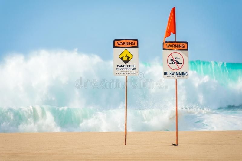 No swimming, dangerous shorebreak. Warning signs indicating no swimming allowed due to huge waves and dangerous shorebreak near the Banzai Pipeline on the North stock photography