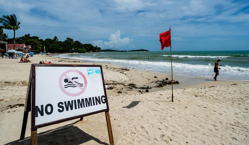 No Swimming at Koh Samui Thailand Beach. `No Swimming` signs & red flags posted due to riptide, undertow & big waves at Koh Samui, Thailand beach stock images