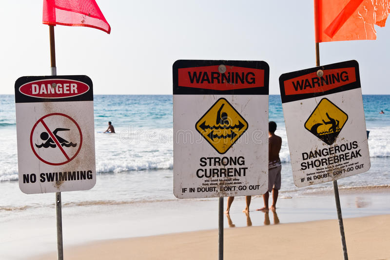 No swimming strong current dangerous shorebreak. Prominent warning signs at beach in Hawaii, with people in and out of the water stock photography