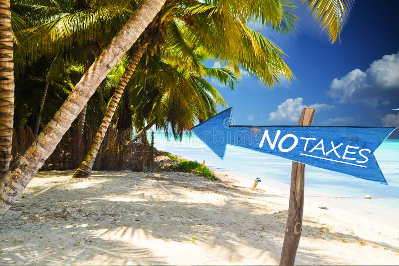 No taxes in a fiscal paradise, exotic island as landscape. No taxes in a fiscal paradise, blue wooden arrow with exotic island as landscape stock photo
