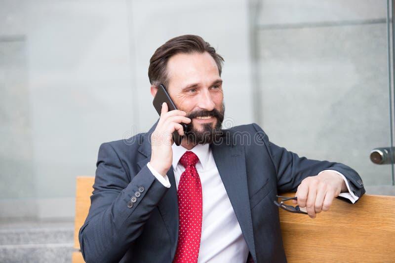 No telefone Retrato do homem de negócios moderno que fala no Smart-telefone ao sentar-se no banco fora homem farpado que guarda v fotografia de stock royalty free