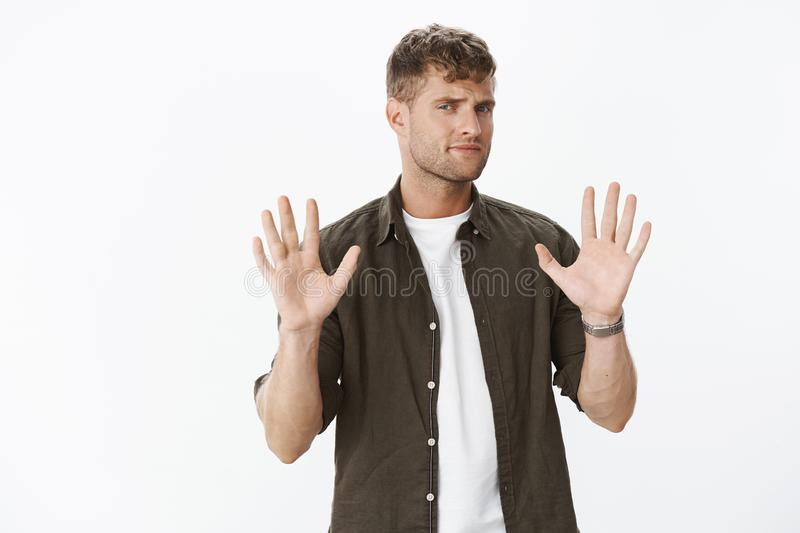 No thanks. Hesitant unimpressed and displeased good-looking male customer raising palms in refusal, frowning and. Grimacing doubtful, rejecting offer being stock images