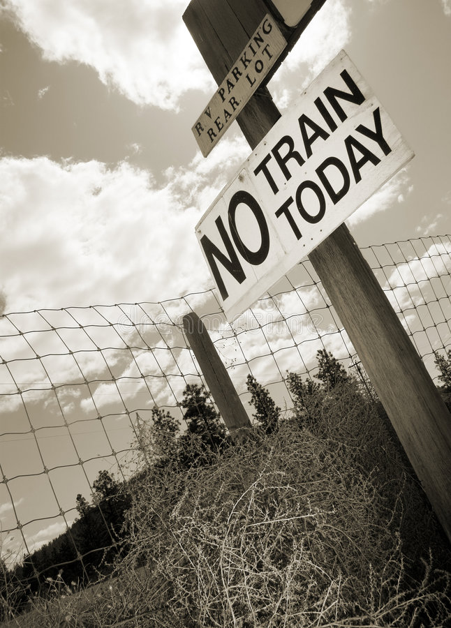 No Train Today. Old signpost with tumbleweed in sepia tone royalty free stock image