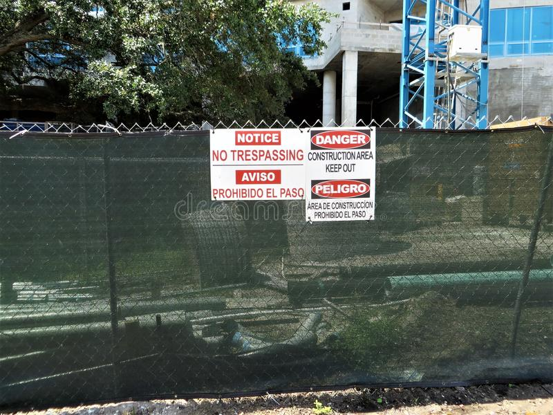 Construction site fence, Tampa, Florida. NO TRESPASSING and DANGER signs in English and Spanish on chain link fence around construction site stock images