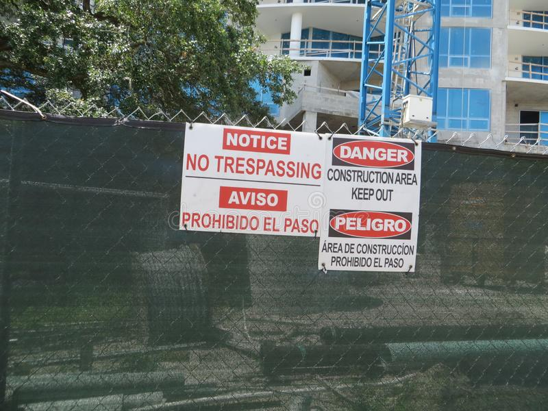 Construction site fence, Tampa, Florida. NO TRESPASSING and DANGER signs in English and Spanish on chain link fence around construction site royalty free stock photo