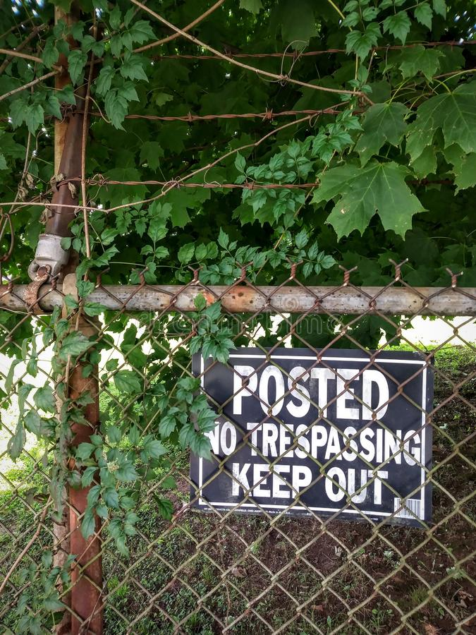 Grungy No Trespassing Sign on Rusty Chain Link Fence. stock image