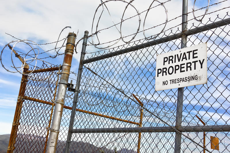 No Trespassing Sign on Fence. Run down metal fence has a sign with no trespassing on it stock photos